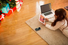 Pretty woman lying on floor using technology at Chritmas Stock Image