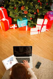 Pretty woman lying on floor using technology at Chritmas Royalty Free Stock Photography