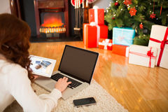 Pretty woman lying on floor using technology at Chritmas Stock Images