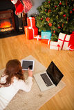 Pretty woman lying on floor using technology at Chritmas Royalty Free Stock Photo
