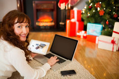 Pretty woman lying on floor using technology at Chritmas Stock Photo