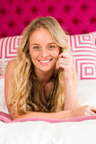 Pretty woman lying on her bed and looking at camera Royalty Free Stock Photography