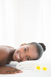 Pretty woman lying on massage table smiling at the camera Stock Images