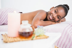 Pretty woman lying on massage table smiling at the camera Stock Photo
