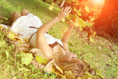Pretty woman lying on meadow with falling leafs in autumn Stock Photos