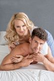 Pretty Woman Lying Over Handsome Partner on Bed Royalty Free Stock Images