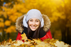 Pretty woman is lying in a yellow autumn leaves Stock Image
