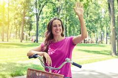 Pretty woman made a stop during bicycle ride to wave somebody Stock Images