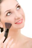 Pretty woman with a make-up brush Royalty Free Stock Photo