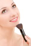 Pretty woman with a make-up brush Stock Images