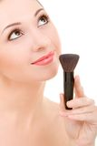 Pretty woman with a make-up brush Royalty Free Stock Images