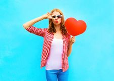 Pretty woman makes an air kiss with a red balloon in the shape Stock Photo