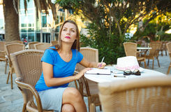 Pretty woman makes notes in a notebook in a cafe Stock Photos
