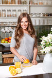 Pretty woman making orange juice Royalty Free Stock Image