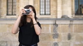 Pretty woman making photo rewinding a film camera on background. Old buildings in Paris on background. Gimbal shot of pretty smiling happy caucasian brunette stock video footage
