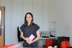Pretty woman making pink leather wallet at home atelier. Pretty craftswoman making pink leather wallet at home atelier. Concept of home handicraft business and Royalty Free Stock Photography