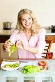 Pretty woman making salad Stock Images