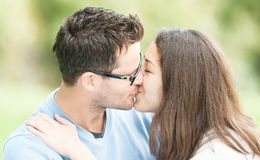 Pretty woman and man in glasses kissing in park. Royalty Free Stock Image