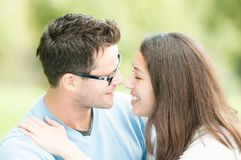 Pretty woman and man in glasses kissing in park. Royalty Free Stock Photos
