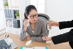 Pretty woman manager having allergy problem. Pretty elegant women manager having allergy problem feeling painful during season change time and colleague giving Royalty Free Stock Images