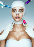 Pretty woman in medical bandages and beauticians hands with syringes making botox injection in her face Royalty Free Stock Photography