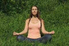 Pretty woman meditating in nature Stock Photo