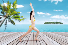Pretty woman meditating at the pier Stock Photography