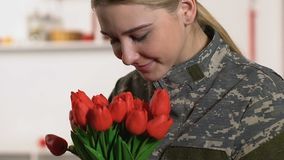 Pretty woman military uniform sniffing tulips bouquet, veterans day, patriotism. Stock footage stock video footage