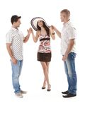 Pretty woman in mini skirt with two men. Pretty woman in mini skirt and straw hat standing with two men in summer shirt, holding hand, smiling, cutout on white Stock Images