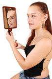 A pretty woman in the mirror. A beautiful young woman touching up her make-up and holding up Royalty Free Stock Images
