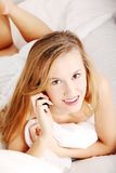 Pretty woman with mobile phone lying on bed Royalty Free Stock Photos