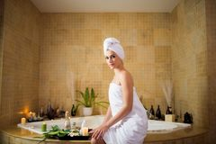 Pretty Woman in Modern Bathroom. Attractive young woman wearing towel looking at camera while sitting on edge of bathtub, interior of modern bathroom on Stock Photos