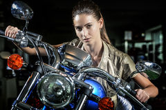 Pretty woman on motorcycle at night. Beautiful female model portrait with motorcycle. Over night time background Royalty Free Stock Image