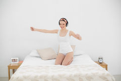 Pretty woman moving on her bed while listening to music Stock Photography