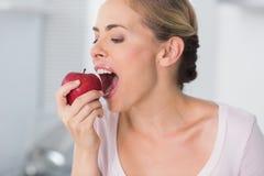 Pretty woman munching apple Stock Photo