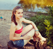 Pretty woman at nature, sitting on stump. Insta-retro filter effect Stock Image
