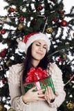 Pretty woman near christmas tree with present Stock Photos