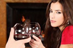 Woman cheers with someone. Pretty woman near fireplace, holding glass of wine and cheers with someone Stock Photo
