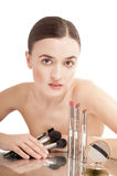 Pretty  woman near the glamour red lipsticks and make-up brushes. Royalty Free Stock Image