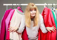 Pretty woman between new clothes. Stock Photo