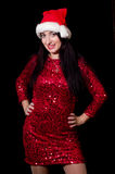 Pretty woman on New Year party. Pretty woman in red dress and Santa hat on the black background Royalty Free Stock Photography