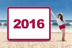 Pretty woman with number 2016 at beach Royalty Free Stock Photos