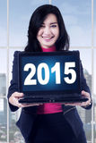 Pretty woman with numbers 2015 on laptop Royalty Free Stock Photo