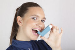 Pretty woman, nurse, using asthma inhaler. Pretty young woman, nurse, showing, using an asthma inhaler for preventing attacks, space for Your text Stock Photo
