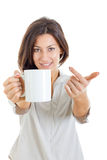 Pretty woman offered white cup of coffee or tea to you or to cam Stock Photography