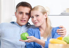 Pretty woman offers an apple to her husband Royalty Free Stock Images