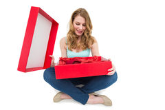 Pretty woman opening a gift smiling at it Royalty Free Stock Photography