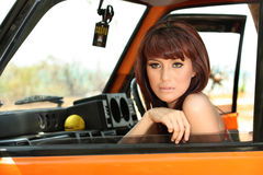 Pretty woman in orange car Stock Images