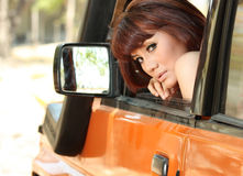Pretty woman in orange car Royalty Free Stock Image