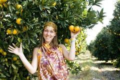 Pretty woman in orange grove smiling Stock Image